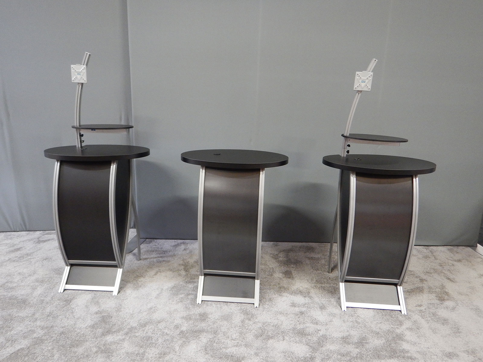"RENTAL: (2) RE-1213 Counters with Black Oval Shelves, 30"" High Curved Extrusion Monitor Mounting Arm, Small Monitor Mount, Black Sintra Infill Panels and Black Laminated Tops, (1) RE-1213 Counter Without Monitor Arm and Mount"
