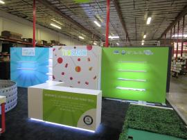 Custom Inline Exhibit with Gravitee and Custom Construction. Design Includes Backlit Logo, Shelves, LED Edge Lighting, Reception Counters with Storage, Closet, and Fabric and Direct Print Graphics